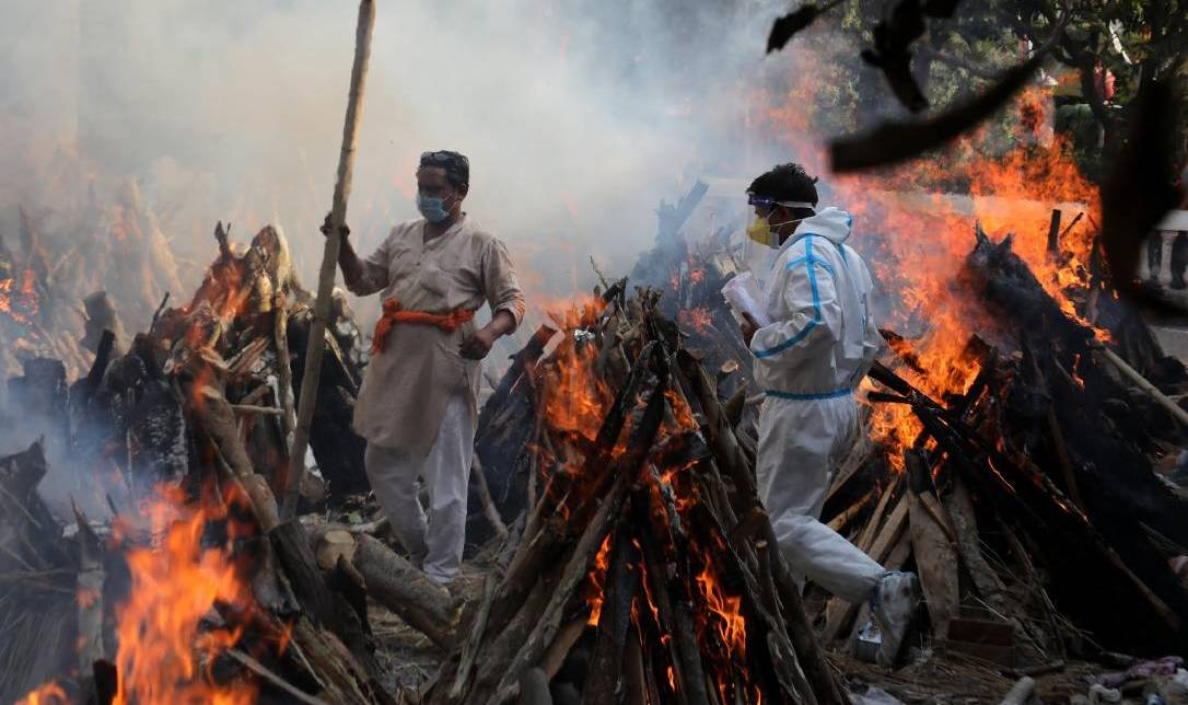 Relatives stand next to the burning funeral pyres of those who died due to COVID-19 at Ghazipur cremation ground in New Delhi. Picture: Getty Images